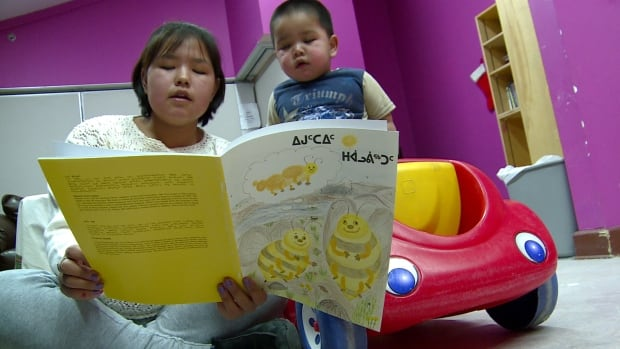Two children read a book in Inuktitut. The writing on the book's cover is in syllabics, which the Nunavut government is looking at phasing out of the school system in favor of Roman orthography.
