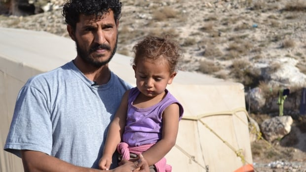 "Abdel, a Syrian father of six children, holds one of his children at the ""informal tented settlement"" where they are currently staying. His family has been living out of a tent with no access to water for about seven months."