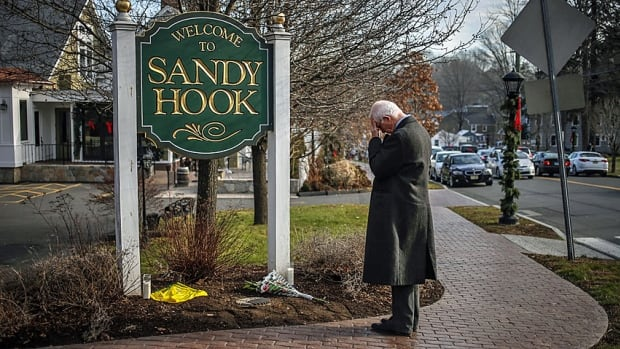 A visitor to Newtown, Conn., pauses to pay his respects to the 26 people, 20 schoolchildren and six teachers, killed by a 20-year-old gunman with mental health problems on Dec. 14, 2012.