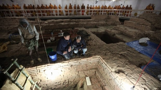 In photo released by National Geographic, archaeologists Robin Coningham, second from right, and Nepalese archaeologist Kosh Prasad Acharya, right, direct excavations within the Mayadevi Temple, uncovering a series of ancient temples contemporary with the Buddha as Thai monks meditate in the background.