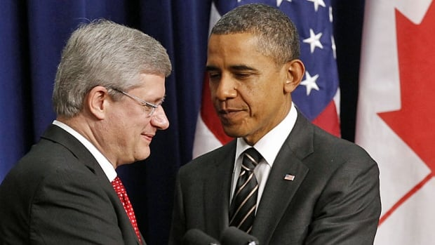 Prime Minister Stephen Harper, left, and U.S. President Barack Obama shook hands on a Beyond the Border deal in Washington in December 2011. But a new report by Public Safety Canada says Canada is behind in implementing parts of the deal.
