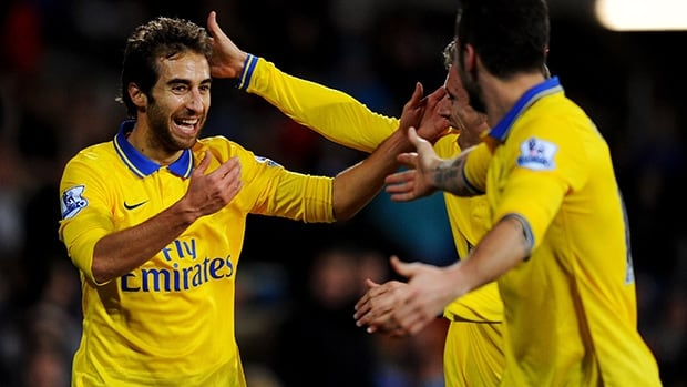 Mathieu Flamini of Arsenal, left, celebrates with teammates after his goal against Cardiff at Cardiff City Stadium on November 30, 2013 in Cardiff, Wales.
