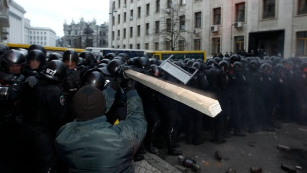 A man holds a stick as protesters try to break through police lines near the presidential administration building during Sunday's rally in Kyiv.