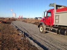 Trucks drive along the future site of a rail line near Tin Can Beach