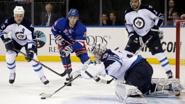 Winnipeg Jets goalie Ondrej Pavelec makes a save as centre Olli Jokinen defends and New York Rangers left wing Chris Kreider skates toward the goal during the second period Dec. 2 in New York.