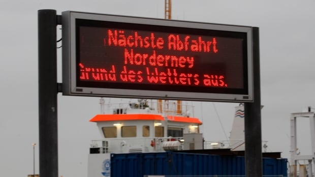A sign in Norddeich, Germany, for the ferry to Norderney island reads 'Next departure to Norderney cancelled due to weather.' The North Sea beach town was preparing for the arrival of Xaver, expected to bring strong winds and high tides.