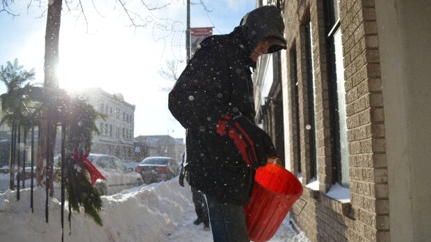 Neil Corbett spreads salt over the sidewalk in front a building he manages on May Street in Thunder Bay. The city received 15 cm of snow overnight Wednesday.
