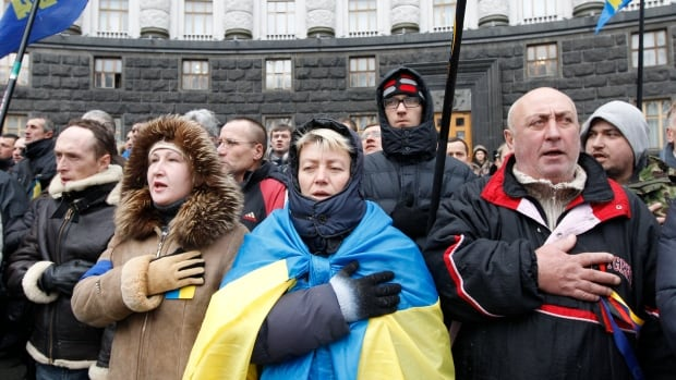 Supporters of Ukrainian EU integration sing and wave flags during a protest in front of the Ukrainian cabinet of ministers building in Kyiv on Friday while their president, Viktor Yanukovich met with Russian President Vladimir Putin to negotiate economic aid to shore up Ukraine's fragile economy.