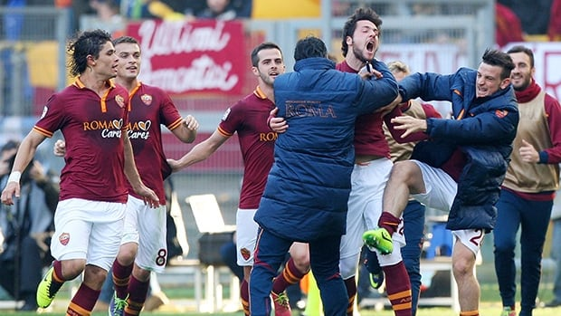 Roma's Mattia Destro, centre, celebrates with teammates after scoring against Fiorentina at Stadio Olimpico on December 8, 2013 in Rome, Italy.
