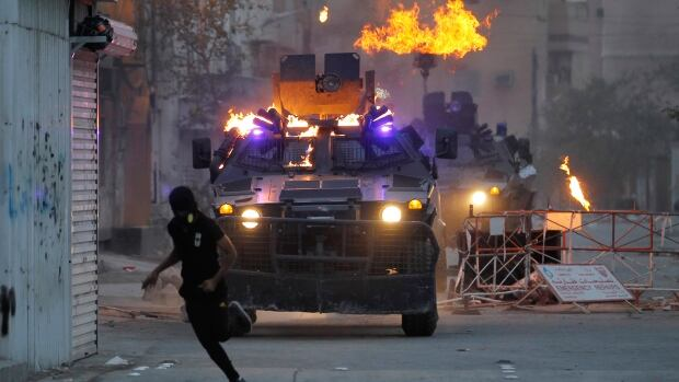 An anti-government protester runs for cover after throwing a molotov cocktail at an armoured vehicle during an anti-government protest in Sitra, Bahrain, in March 2012. Canada's arms sales to Bahrain shot from zero in 2011 to $250,000 in 2012.