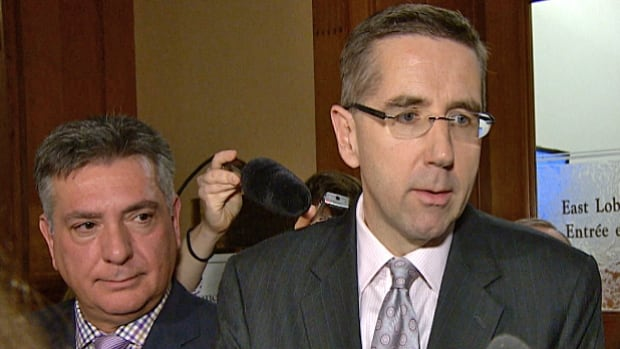 John Milloy, the minister of government services, is seen speaking with reporters Monday about the Liberals' intention to bring forward legislation to limit the compensation of senior executives within the broader public sector. Finance Minister Charles Sousa is seen standing on the left-hand side of the image.