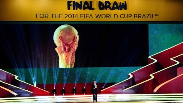 Spain coach Vicente del Bosque holds the World Cup trophy on stage before the Final Draw for the 2014 FIFA World Cup at Costa do Sauipe Resort last week in Costa do Sauipe, Bahia, Brazil.
