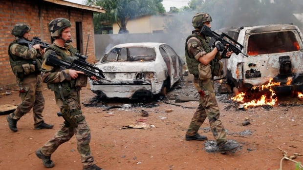 French troops patrol past two Seleka, the alliance of mostly Muslim rebel groups, vehicles set on fire Monday by Christian mobs in Bangui, Central African Republic.
