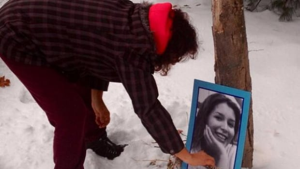A woman lights a candle for Kelly Morrisseau on Dec. 10, 2013, seven years after her death. The case remains unsolved.