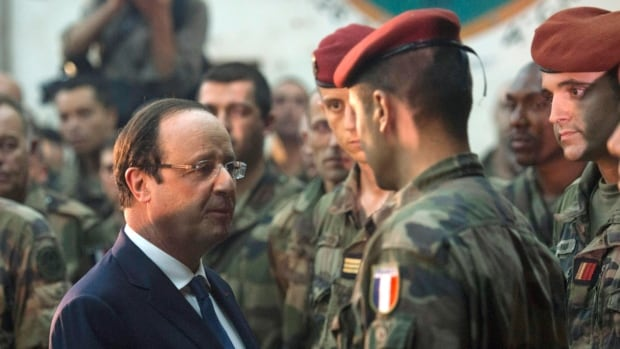 French President Francois Hollande, left, speaks with French soldiers after paying tribute to two members of the French forces who were killed in an attack by gunmen in the capital, Bangui. They were France's first casualties in an operation to restore stability in its former colony, which has been racked by fighting between Muslims and Christians.