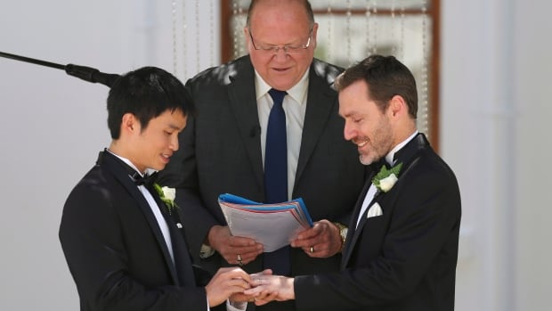 Same-sex celebrant Rodger Munson, centre, watches Chris Teoh, left, put a wedding ring on Ivan Hinton's finger as they take their vows during a ceremony at Old Parliament House in Canberra, Australia, on Dec. 7. Australia's High Court on Dec. 12 overruled the state law permitting same-sex marriage.