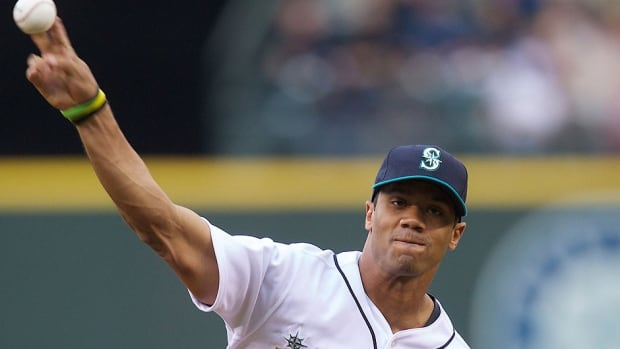 Seahawks quarterback Russell Wilson, seen here throwing out the ceremonial first pitch before a June 7, 2013 game in Seattle, was selected by Texas from Colorado in the Rule 5 draft Thursday. Wilson played minor league baseball for parts of two seasons before becoming an NFL star.