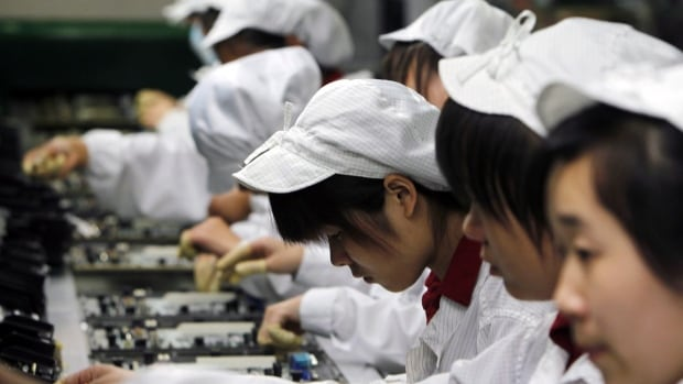 Staff members work on the production line at the Foxconn complex in Shenzhen, China in 2010. The average work week is 60 hours and a labour group is calling on the Apple supplier to get hours of work down.