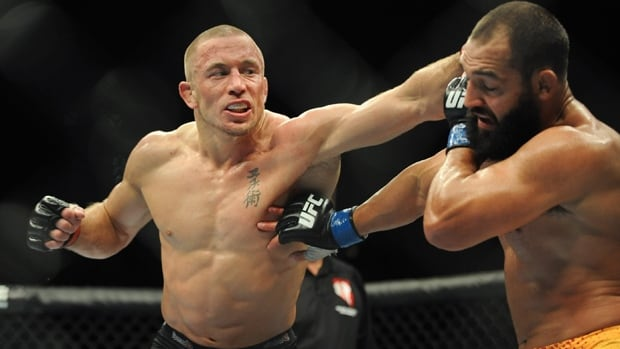 Georges St-Pierre, left, lands a punch on Johny Hendricks in their welterweight title fight in UFC 167 at Las Vegas on Nov. 16. The Montreal fighter is stepping away from the octagon for a mental break but vowed on Friday he would return.