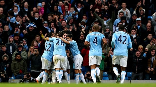 Fernandinho of Manchester City celebreates with teammates after scoring their fifth goal against Arsenal at Etihad Stadium on December 14, 2013 in Manchester, England.