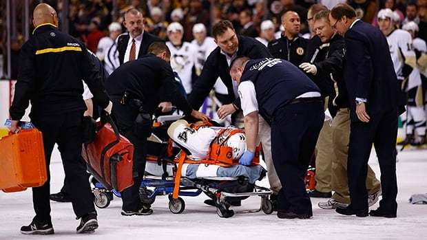 Brooks Orpik of the Pittsburgh Penguins is carted off of the ice on a stretcher after the altercation with Shawn Thornton of the Boston Bruins on December 7, 2013 in Boston.