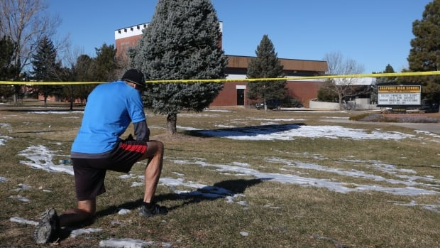 Sean Sweeney, a runner who lives near Arapahoe High School in Centennial, Colo., pauses to say a prayer for the victims and the gunman of a shooting at the school that left the student gunman dead and two other students injured.