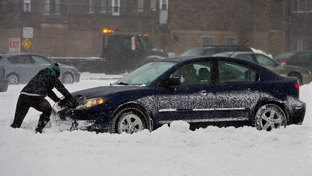 A passenger pushes a car in a parking lot in Halifax on Sunday. Environment Canada is forecasting freezing rain and ice pellets for the Maritimes this weekend.