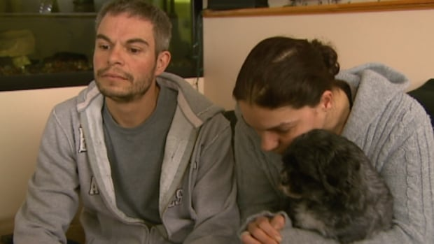 Rick Ducharme and Sonia Chaves (cuddling the couple's other dog) are offering a $2,500 reward for the return of Boo.