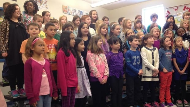 Students at St. Joan of Arc School sang Christmas songs as provincial officials announced a new school to be built in Aspen Woods.