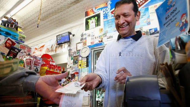 Keith Ganatra, owner of the Del Monte Market, sells Mega Millions lottery tickets at a brisk pace on Tuesday in Laveen, Ariz. The jackpot was at an estimated $636 million, the second-biggest lottery prize in U.S. history.