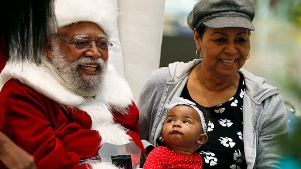 African-American Santa Claus Langston Patterson, 77, poses with four-month-old Raelyn Price and her grandmother, Gloria Boissiere, in an L.A. mall. His beard is real, too.