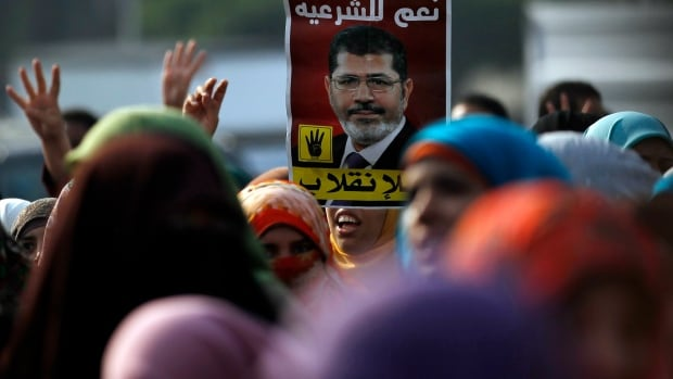 Ousted Egyptian president Mohammed Morsi, shown on a poster during a protest in Cairo in November, on Wednesday was ordered to stand trial on charges including conspiring with foreign organizations to commit terrorist acts in Egypt.