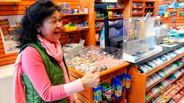 Owner Young Soo Lee basks in the attention at her small Alliance Center office building newsstand on Wednesday in Atlanta, Ga., after lottery officials said one of two winning Mega Millions lottery tickets were purchased from her store in Tuesday's $636 million draw.