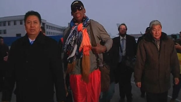 Former NBA star Dennis Rodman is greeted at the airport by dignitaries upon arriving in Pyongyang, North Korea, on Thursday.