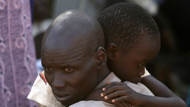 An internally displaced man holds his son in Juba. South Sudanese government troops battled to regain control of a provincial capital on Thursday, the fifth day of a conflict that that has deep-ended ethnic divisions in the two-year-old nation.