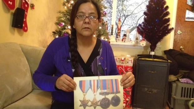 Marissa Fitzner holds a photograph of her father's Second World War medals.