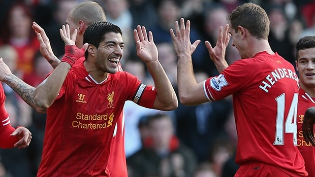 Luis Suarez of Liverpool, left, celebrates after scoring his second goal against Cardiff City at Anfield on December 21, 2013 in Liverpool, England.