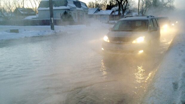 A van passes through a street flooded by a watermain break on Monday morning.