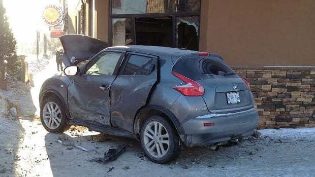 A car sits on the sidewalk at Osborne Street and River Avenue after a crash that sent it into a building.