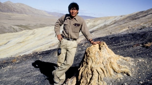 Dr. Tatsuo Sweda, then of Nagoya University, Japan, poses with a fossilized stump found near Strathcona Fiord on Nunavut's Ellesmere Island in 1990. The region has been hailed as 'a paleobiological hotspot.'