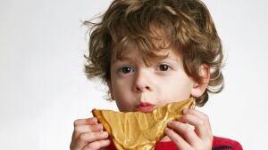 Boy eating peanut butter.