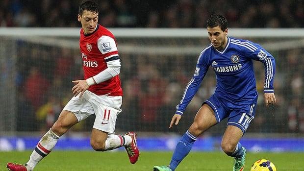 Arsenal's midfielder Mesut Ozil, left, challenges Chelsea's midfielder Eden Hazard, right,  during a Premier League match in London, on Monday.