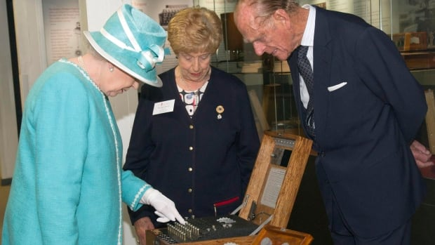 Queen Elizabeth and Prince Philip examine a German Enigma encoding machine in 2011. Alan Turing's team were able to break the code during the Second World War.