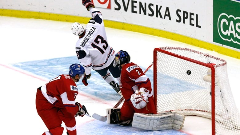 623c66590 Vince Hinostroza of the U.S. scores on Czech Republic s goalie Daniel  Dolejs (R) and Libor Sulak (L) during the third period of their IIHF World  Junior ...
