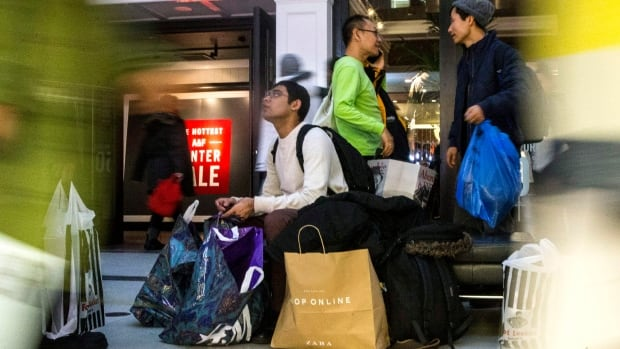 A shopper rests with his bags after an early visit to the Boxing Day sales at the Eaton Centre in downtown Toronto on Thursday.