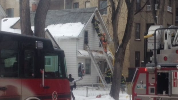 Firefighters access the attic of a two-storey home on Beverley Street on Friday afternoon.