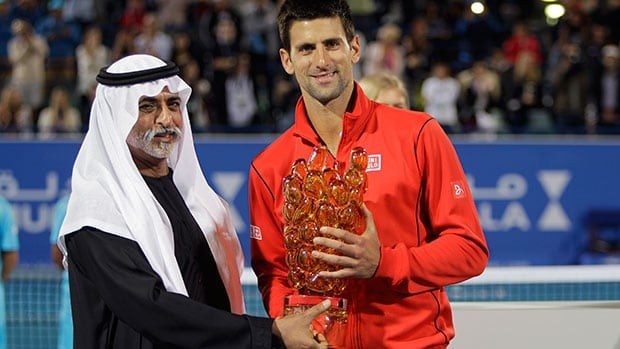 Novak Djokovic of Serbia, right, receives the winner's trophy from Sheikh Hamdan bin Mubarak Al Nahyan, UAE Minister of Higher Education and Scientific Research, after he beat David Ferrer of Spain Saturday in Abu Dhabi, United Arab Emirates.