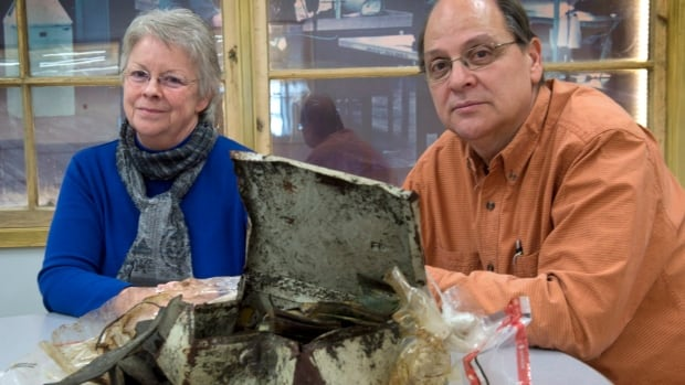 Diane Roy and Pierre Paquet look over the petty-cash box that was recovered from Lac-Megantic's only library consumed by flames in July after a runaway tanker train derailed, exploded and destroyed part of the Quebec town. The dented metal box contained about $500 in rolls of coins and oily bills.