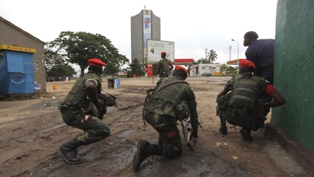 Congolese security officers position themselves as they secure the street near the state television headquarters in the capital Kinshasa. Congo is struggling to emerge from decades of violence and instability.