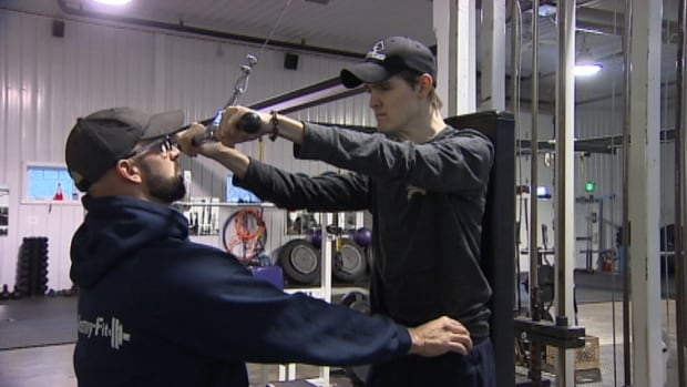 Kyle Jay of Charlottetown works out with trainer Jason Mosher. Jay suffered a brain stem stroke when he was 18 years old, but has made an inspirational recovery.